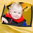 Little boy looking out of yellow tent