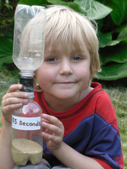 Young boy holding home-made sand timer