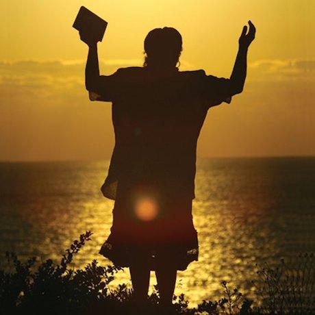 Man praying overlooking the ocean at sunset