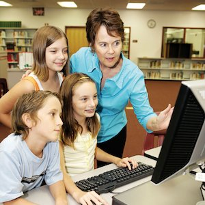 Teacher and children around a computer